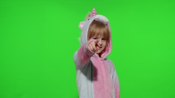 Malá holčička se usmívá, ukazuje na kameru, dělá gesto pistole rukama v pyžamu jednorožce
