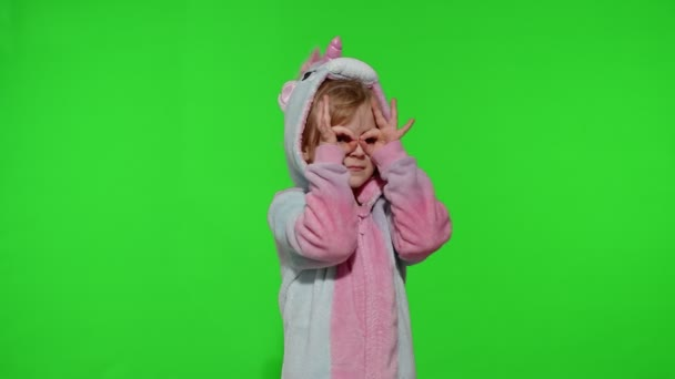 Child girl in unicorn pajamas fooling around, looks through her hands as if through binoculars