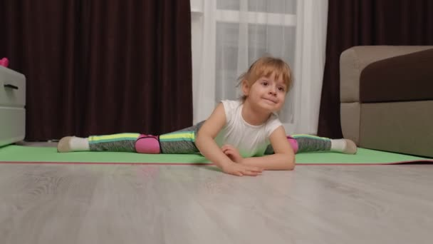 Child kid training gymnastics stretching twine at home, children girl making sport workout exercises