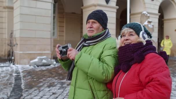 Idős pár turisták nagymama nagyapa fotózás retro kamera télen város