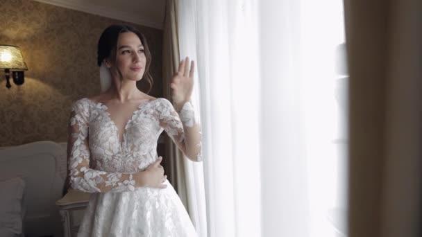 Nevěsta v budoárových šatech u okna. Svatební ranní přípravy. Žena v noční košili a závoji