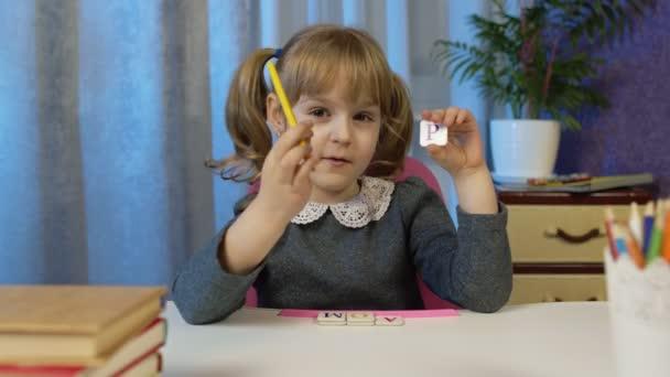 Child girl doing school homework teach alphabet letters with teacher at home, video call by webcam