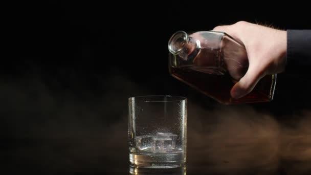 A csapos whiskey konyakot önt a palackból az ivópohárba, jégkockákkal sötét alapon.