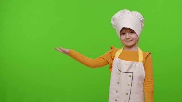 Child girl dressed like chef cook pointing at left on blank space, place for your advertisement logo