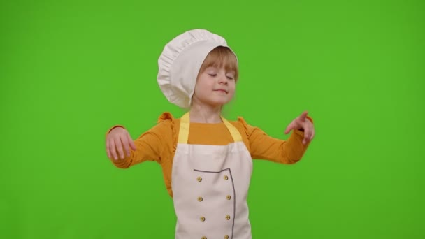 Child girl kid dressed in apron and hat like chef cook baker raising hands, showing tasty gesture