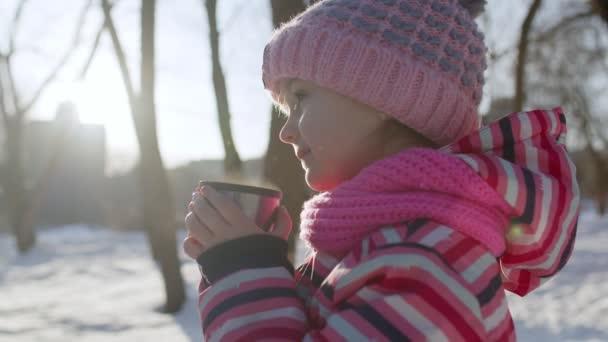 Lächelndes Kindermädchen trinkt Heißgetränk Tee aus Tasse und versucht, sich im winterlichen Parkwald warm zu halten