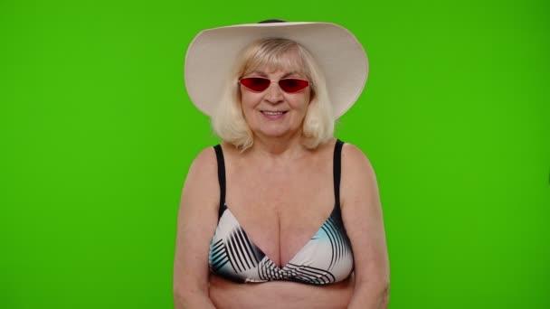 Reife Urlauberin mit roter Sonnenbrille, in die Kamera guckend, lächelnd, lachend