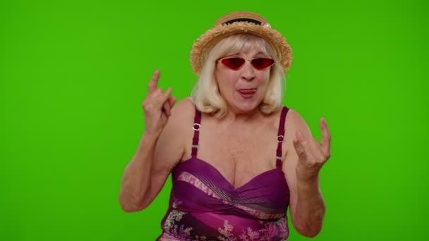 Senior női turista fürdőruha tánc, ünneplés, bemutató nyelv, rock and roll kéz gesztus