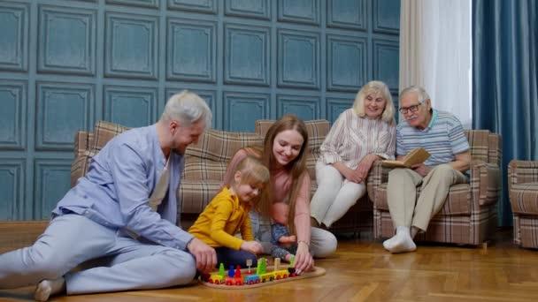 Boldog családi szabadidő otthon gyermek lánya játszik anya és apa vasúti játék a padlón