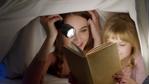 Mladá matka čtení dobrou noc příběh pohádka pro dítě dcera pod peřinou přikrývka v nočním pokoji