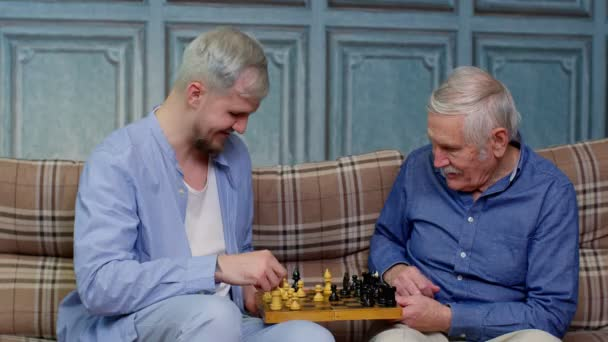 Boldog különböző férfi generációk család idősebb apa és felnőtt fia vagy unokája sakkozik