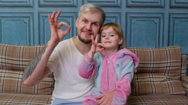Apa és kislánya gyerek pizsamában ül a kanapén a szobában mosolyogva mutatja rendben gesztus jel