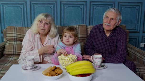 Grandparents watching cartoons movies on TV television with granddaughter at home, happy laughing
