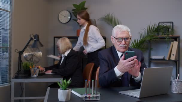 Senior businessman grandfather with mobile phone texing message working watching video communicating