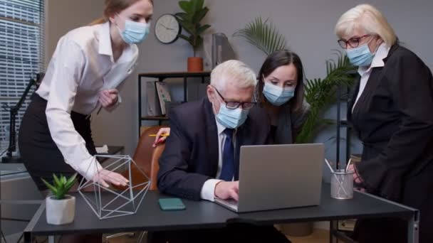 Group business people communicate working with laptop in office in masks during coronavirus pandemic