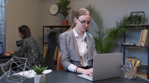 Joyful business woman freelancer concentrated developing new project while looking on laptop screen