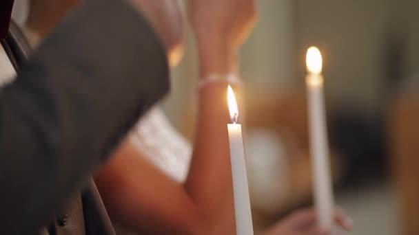 Frischvermählte, Braut und Bräutigam stehen und beten in der Kirche, halten Kerzen in Händen, Trauung