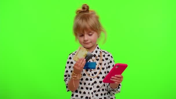 Kleines Teenie-Kind beim Online-Einkauf mit Kreditkarte und Smartphone