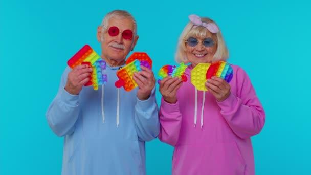 Usmívající se starší babička dědeček drží antistresový dotykový displej push pop to populární hračka