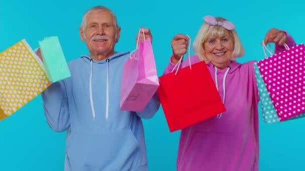 Großvater zeigt Einkaufstüten, Werbepreisrabatte, Black-Friday-Verkauf