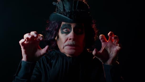 Beängstigender älterer Mann mit Halloween-Hexer-Make-up versucht Angst zu verbreiten und zeigt schwarze, schmutzige Zunge