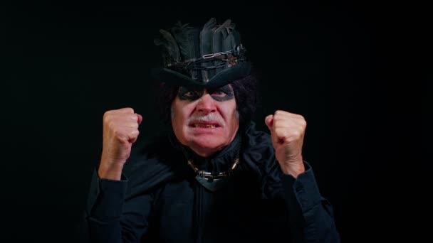 Verärgerter finsterer Mann mit gruseliger Halloween-Hexenschminke hebt die Hände, streitet, streitet