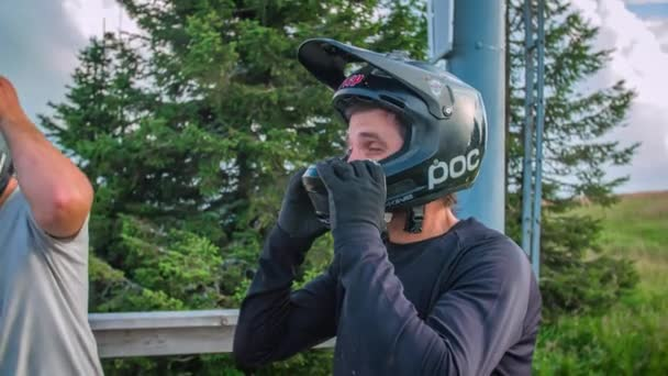 Slow Motion of adult men Putting On Downhill Full Face Helmet On Whilst Talking To Hi Friends In Kope, Slovenia .