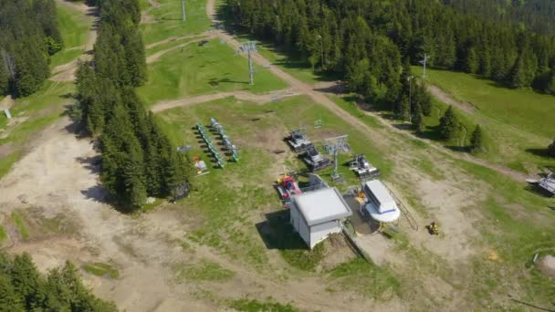Aerial view of two mountain bikers arrive at the summit of the Kope downhill park on a ski lift in the summer, Drone Tracks from above