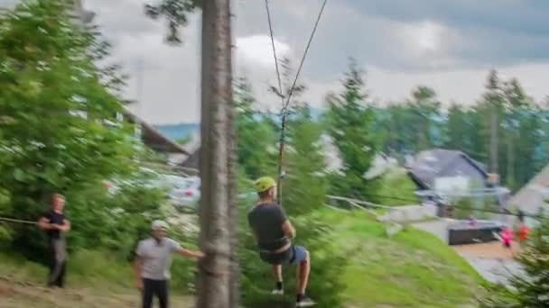 Slow motion of young man hanging from the zip line and swings at Kope, Slovenia.