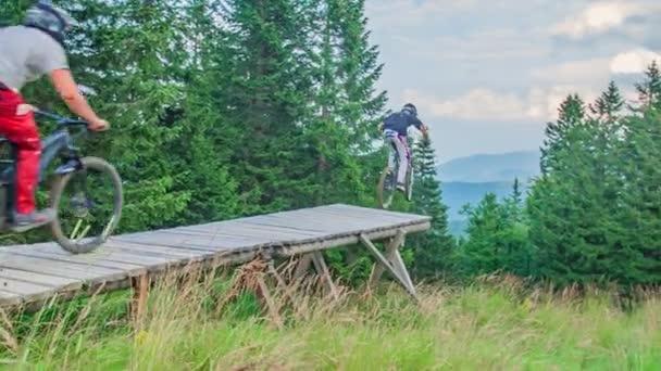 Zpomalený záběr tří odvážných motorkářů skákajících z rampy na horském kole