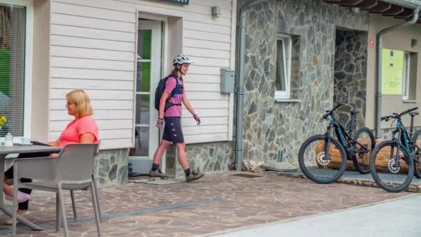 Zwei junge Touristen kommen aus der Rezeption, um in Slowenien, dem nachhaltigsten Land der Welt, E-Bikes zu fahren