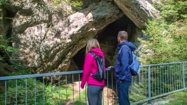 Fiatal pár áll és nézi Huda Luknja barlang, Szlovénia, majd mozog ki lövés balra, lassú pan jobbra barlang, lassított felvétel