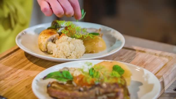 Zblízka záběr kuchaře ruce zdobení slovinské jídlo s bylinkami a listové zeleně. Zpomalený pohyb