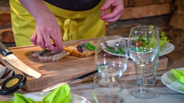 Žena rukou zdobí dva plátky domácího chleba bylinkami a jedlými květinami
