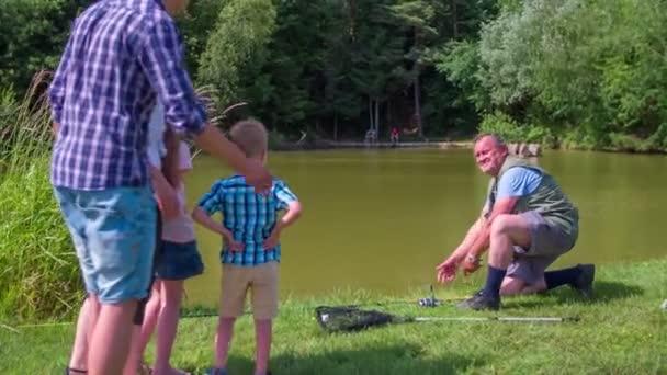 Familie und Fischer in Teichnähe