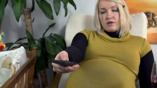 Future mother watching television and eating some nuts