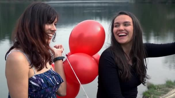 women holding red balloons