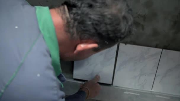 Uomo è posa piastrelle di ceramica applicata con colla speciale