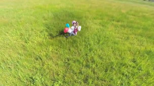 couple with balloons running on grass field