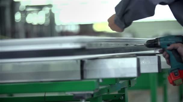 Worker screwing a screw into fetters