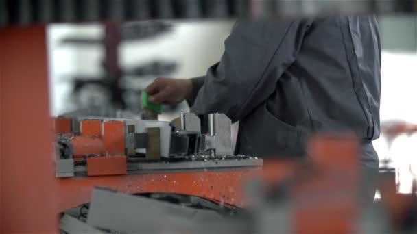 Worker is cleaning metal fetters with air gun