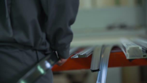 Pracovník klade pružný pás na speciální rám