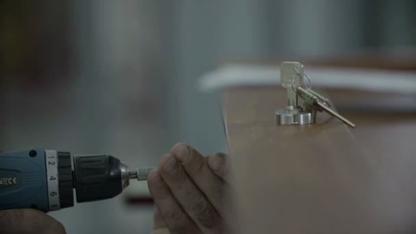 Člověk spojuje zámek s třemi klíči