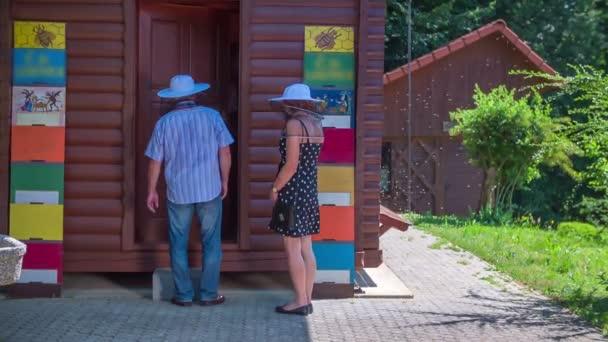 Paar steht vor einem Bienenhaus und der Buchhalter öffnet die Türen