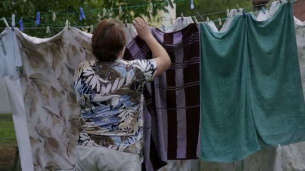 Frau hängt Wäsche an Wäscheleine