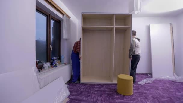 Männer bauen neue Möbel auf