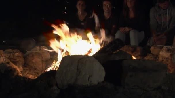 Teenagers singing  around open fire