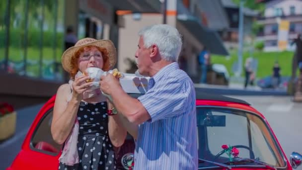 An eldery couple is enjoying themselves eating doughnuts