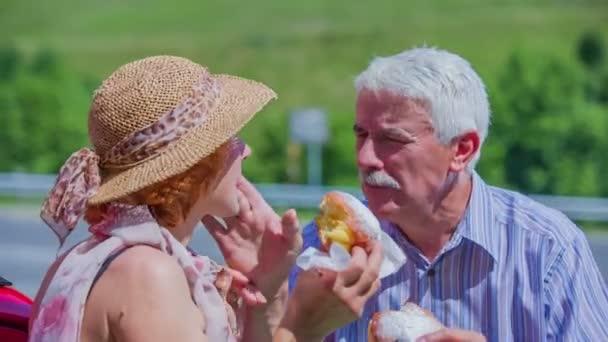 Ein älteres Ehepaar ist Krapfen Essen