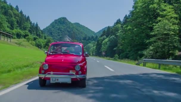 Malé červené auto jede na venkovské silnici
